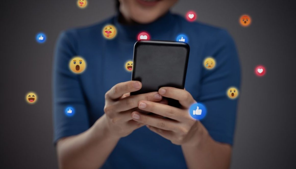 Asian woman using smart phone for social media with emoticon bub